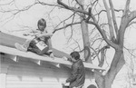 Two men roofing a house